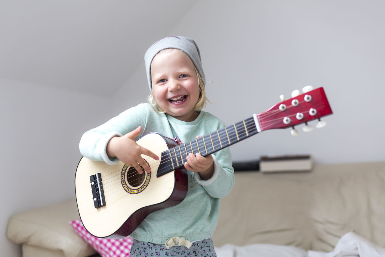 Portrait Of Happy Girl Playing Guitar At Home