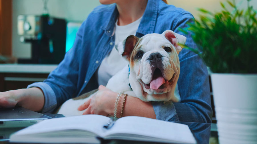 Midsection of woman with dog sitting on book
