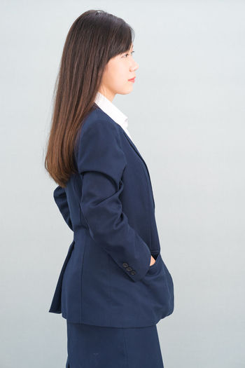 Side view of a beautiful young woman over white background