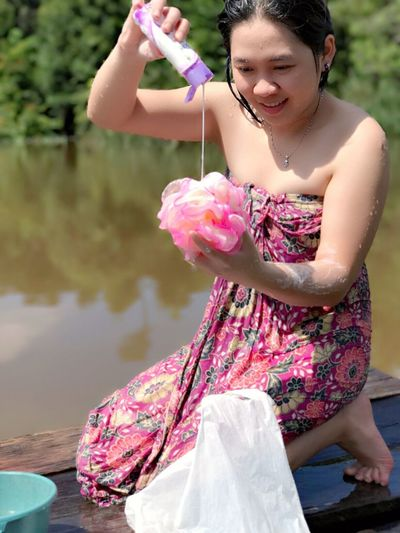 Smiling young woman pouring body lotion on loofah while kneeling at jetty over lake