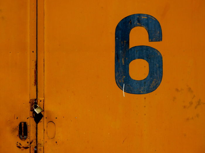 Close-up of orange metal door with number 6