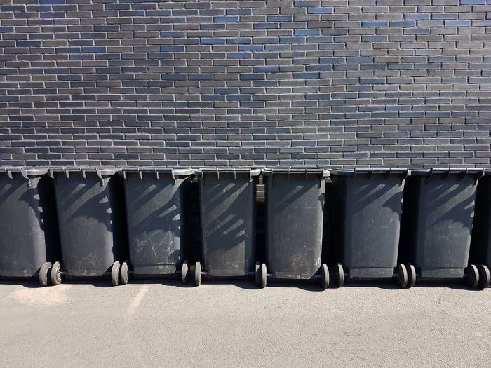 Black Garbage bin in a row in front of a black brick wall Architecture Built Structure Day Sunlight Building Exterior Pattern Nature No People Outdoors In A Row Side By Side Business City Roof Building Shadow Repetition Safety Transportation Wall - Building Feature Garbage Bin Black Black Background