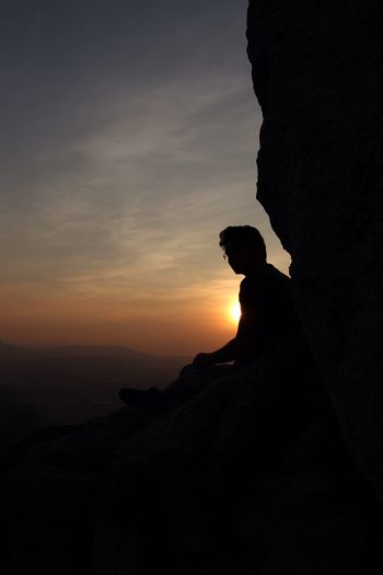 Silhouette man on rock against sky during sunset