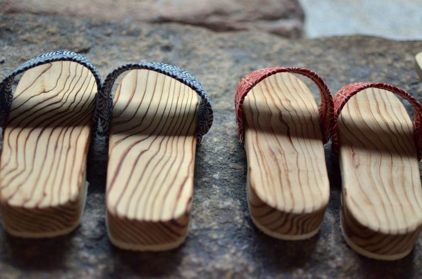 Pairs of wooden slippers rest on stone steps next to a Japanese garden Close-up Side By Side Group Of Objects No People Still Life Wooden Slippers Japanese Culture Full Frame Japan Traditional Clothing Footwear Natural Materials
