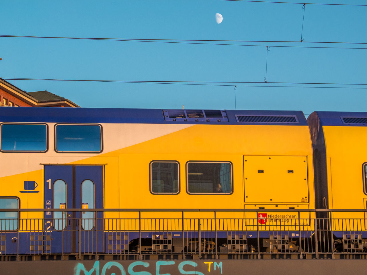 transportation, train - vehicle, mode of transport, public transportation, rail transportation, outdoors, cable, blue, day, railroad track, no people, sky, yellow, stationary, clear sky, built structure, nature, architecture