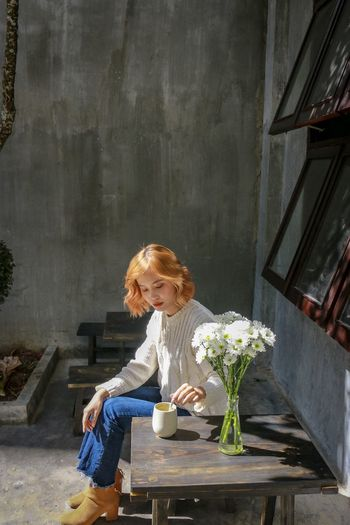 Full length of woman sitting by potted plant