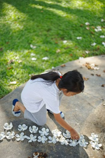 High Angle View Of Girl Arranging Flowers On Footpath