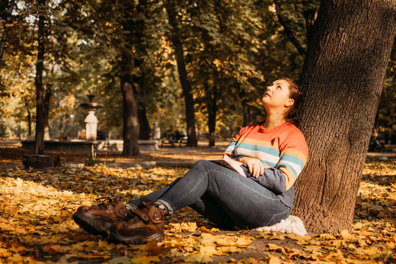 Body shaming, low self-worth concept. sad plus size woman walking in autumn park.