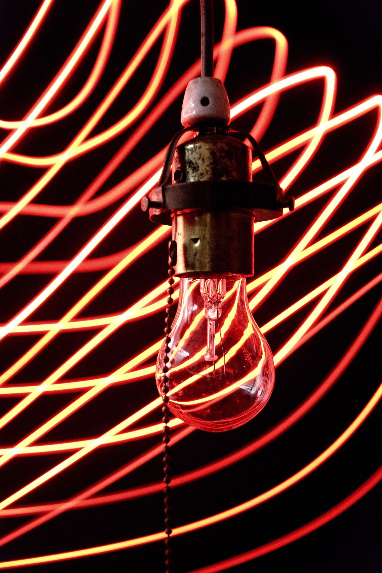 Close-up of electric bulb by light trails against black background