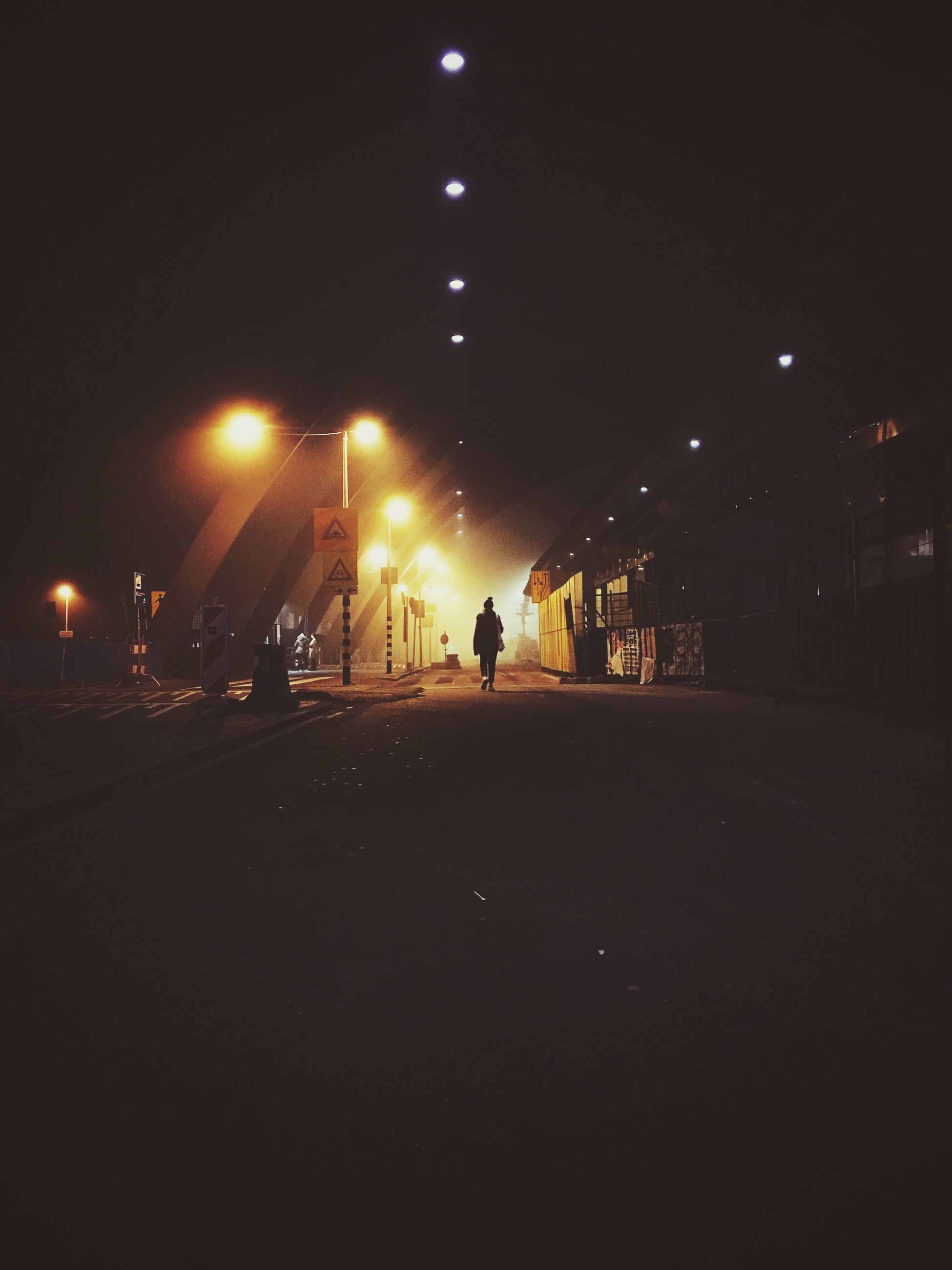 night, illuminated, street light, men, silhouette, street, walking, lifestyles, city, building exterior, the way forward, architecture, built structure, dark, lighting equipment, road, transportation, unrecognizable person, full length