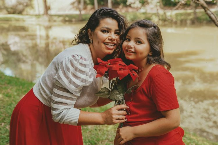 Portrait of smiling mother and daughter holding flowers outdoors