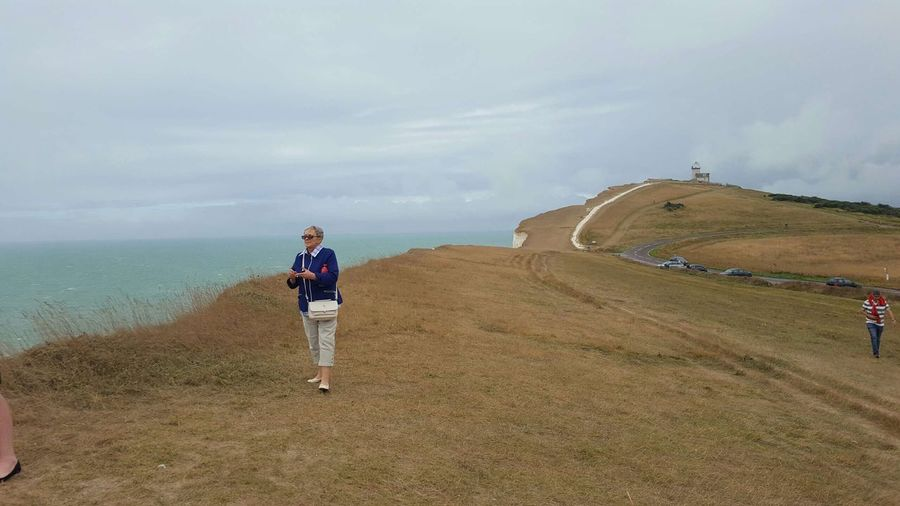 Full length of woman standing on cliff by sea against cloudy sky