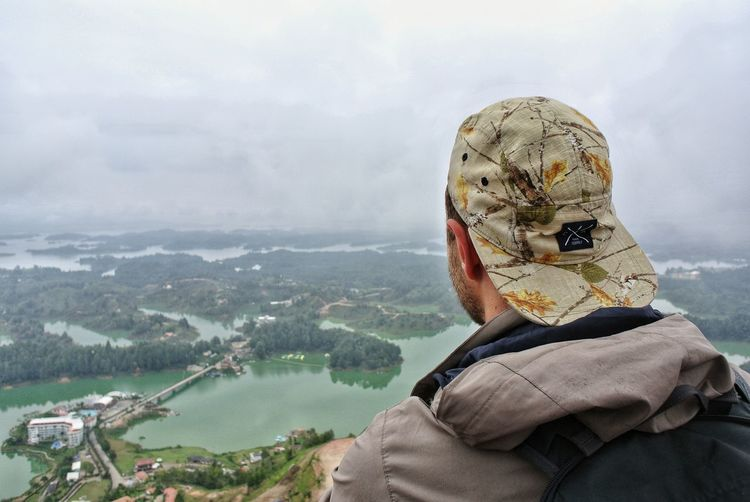 Portrait of man looking at mountain against sky