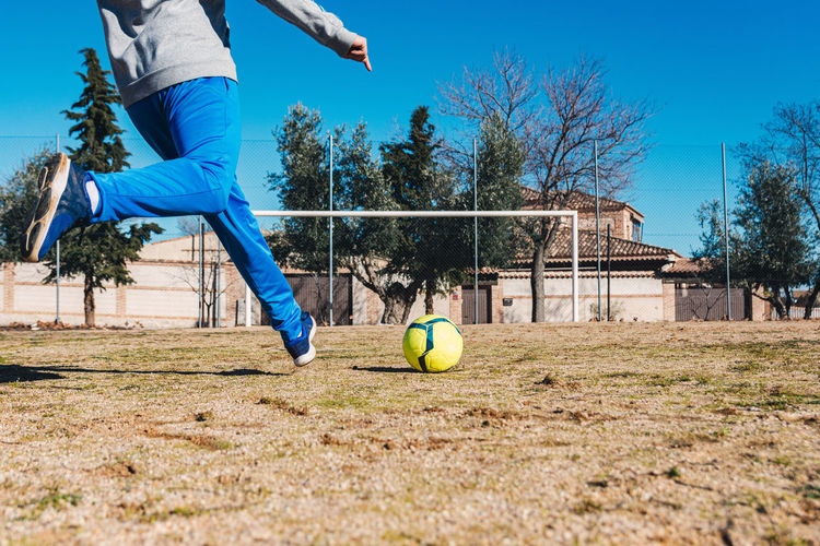 Low section of man playing soccer ball against blue sky