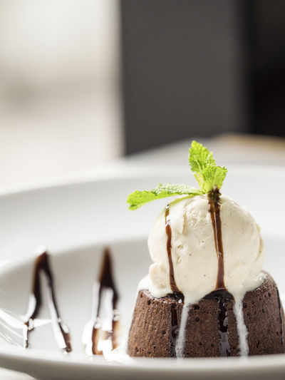 Close-up of ice cream and brownie with chocolate icing served in plate
