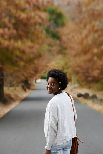 Portrait of smiling woman standing outdoors during autumn