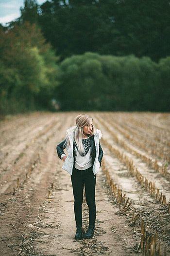 Full length portrait of happy girl standing in farm