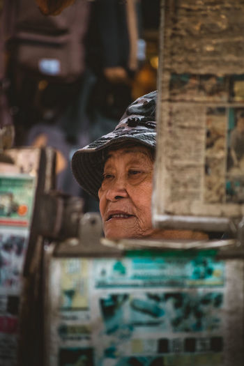 Elderly woman hiding behind her food stall in Chinatown in Kuala Lumpur, Malaysia. Kuala Lumpur Kuala Lumpur Malaysia  NIKON D5300 Nikon Street Market Street Portrait Travel Photography Woman's Face Bokeh Photography Chinese Chinese Woman Close-up Elderly Woman Flea Market Focus On Foreground Grandmother Headshot One Person People Real People Real People Photography Street Photography Street Seller Travel Destinations Urban Photography EyeEmNewHere This Is Aging Visual Creativity This Is My Skin The Portraitist - 2018 EyeEm Awards The Traveler - 2018 EyeEm Awards The Street Photographer - 2018 EyeEm Awards This Is Strength