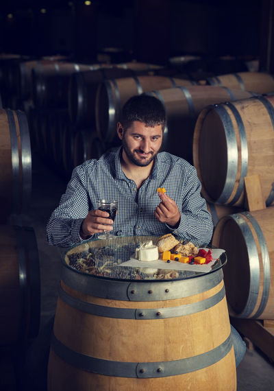 Portrait of man eating food on barrel