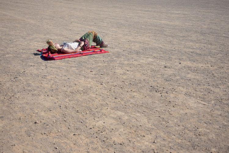 High angle view of boy lying on sand