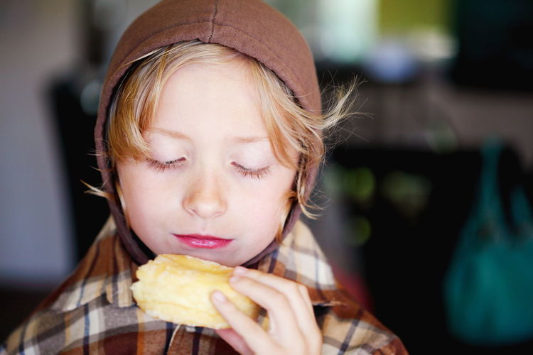 Close-Up Of Boy Holding Donut At Home