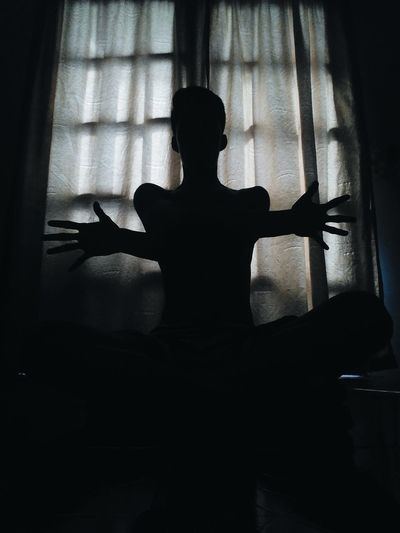 Rear view of silhouette woman sitting at home