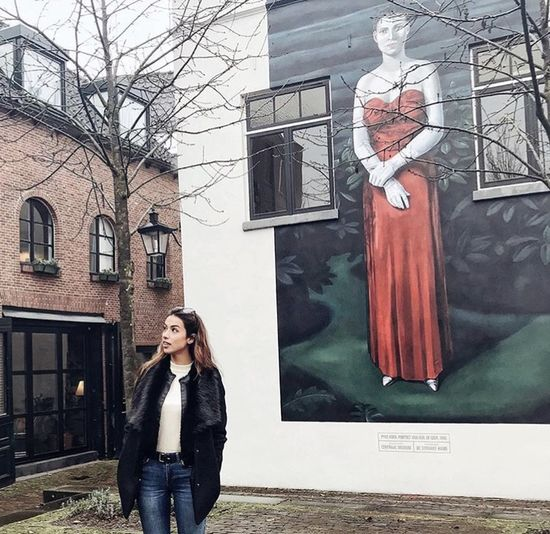 Full length of woman standing by bare tree in city
