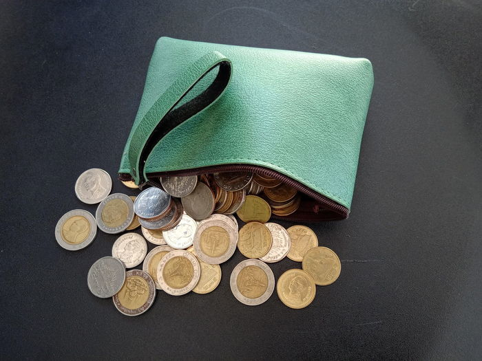 High angle view of coins spilling from purse on table