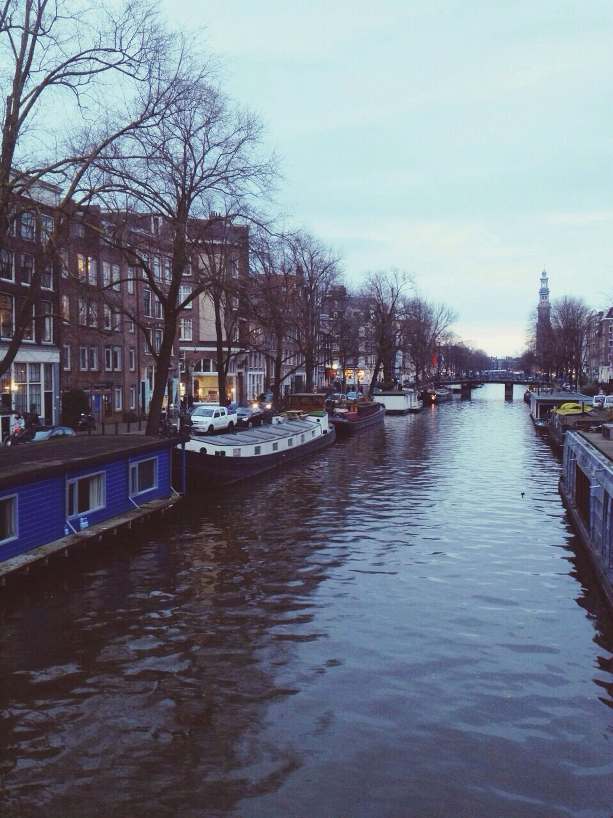 water, architecture, built structure, building exterior, tree, canal, waterfront, bare tree, transportation, river, sky, city, reflection, mode of transport, bridge - man made structure, nautical vessel, rippled, day, connection, outdoors