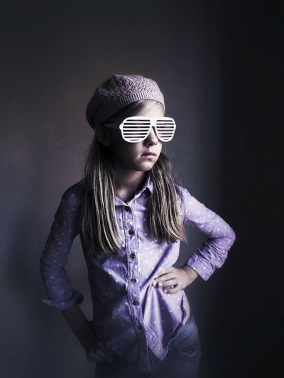 Girl in striped sunglasses looking away over grey background