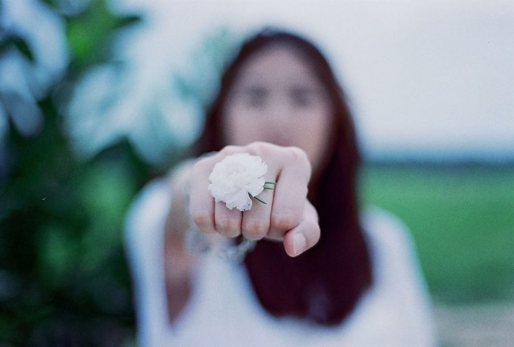 Close-up of woman clenching fist while holding white flower