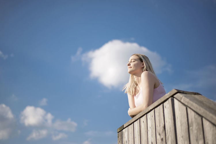 Low angle view of beautiful woman standing against sky