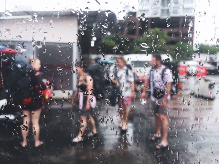 People seen through wet glass window in rainy season