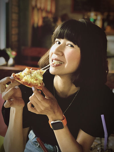 Portrait of young woman eating food in restaurant