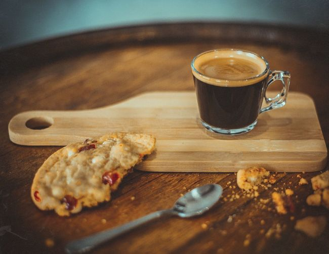 Close-up of coffee cup and cookie on serving board