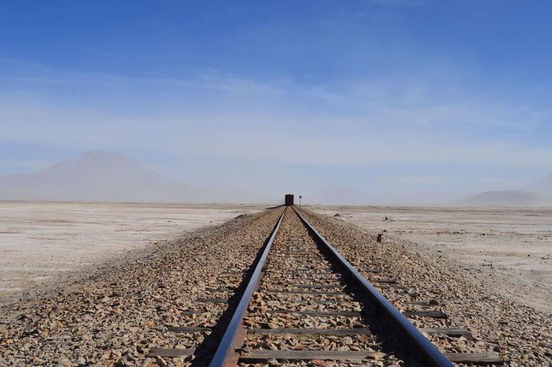 Train on railroad tracks in desert against sky