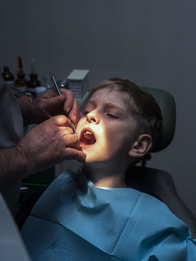 Midsection Of Male Dentist Examining Boy At Hospital