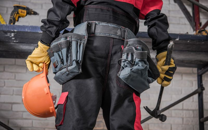 Midsection of worker holding equipment