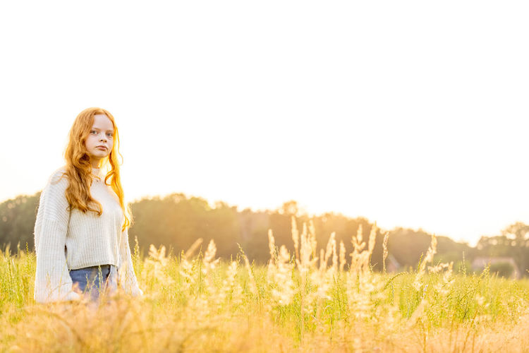 Young woman in grass on field against sky