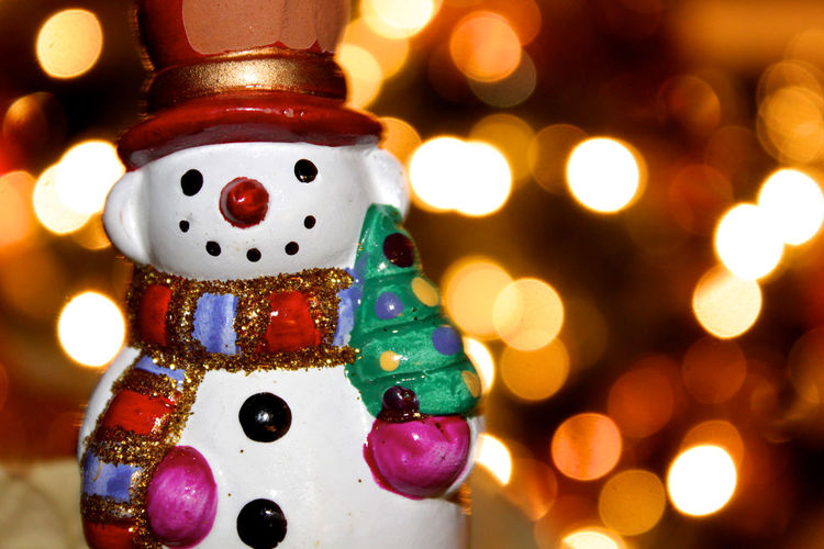 Close-Up Of Snowman Figurine Against Illuminated Christmas Lights At Night