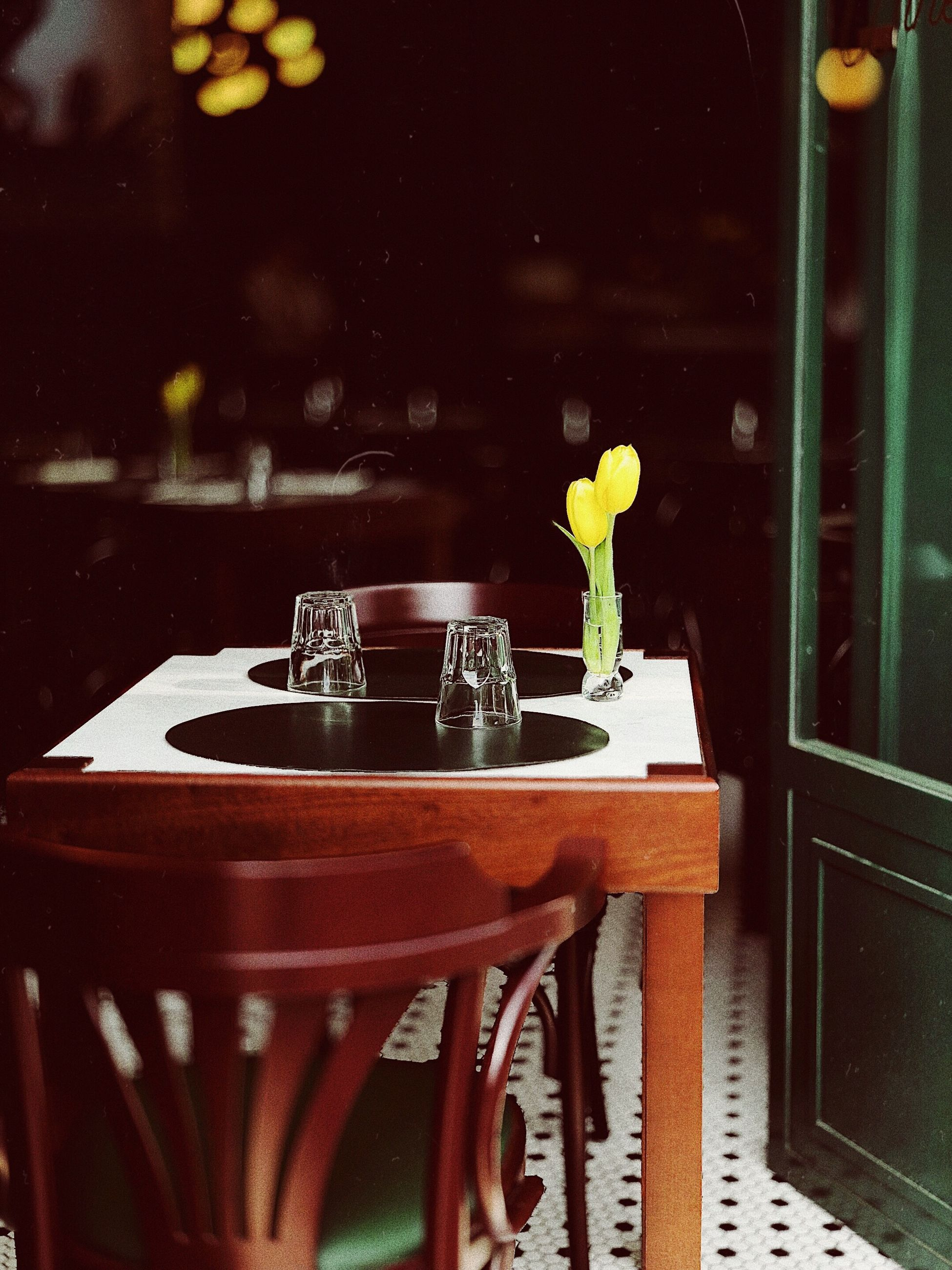 table, no people, chair, restaurant, indoors, flower, vase, plant, food and drink, seat, flowering plant, still life, nature, drink, freshness, glass - material, household equipment, refreshment, container, absence, glass, flower head, crockery