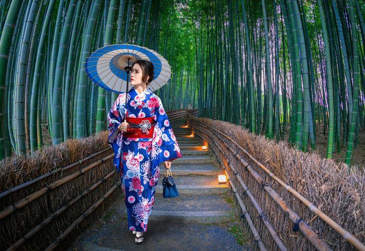 Full length of woman in kimono walking on footpath