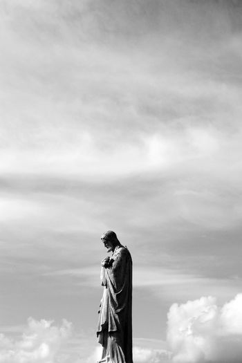 Cloud - Sky Day Human Representation Lifestyles Low Angle View Nature One Person Outdoors People Real People Sculpture Sky Standing Statue