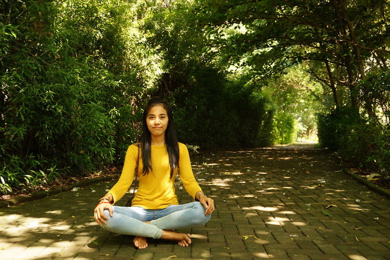 Portrait Of Woman Sitting On Footpath At Public Park