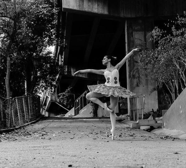 Full length of ballet dancer dancing on street against bridge