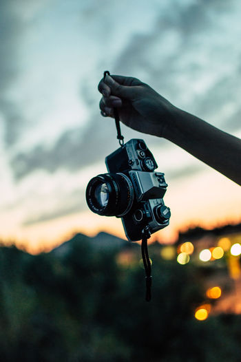 Close-up of hand holding camera against sky during sunset