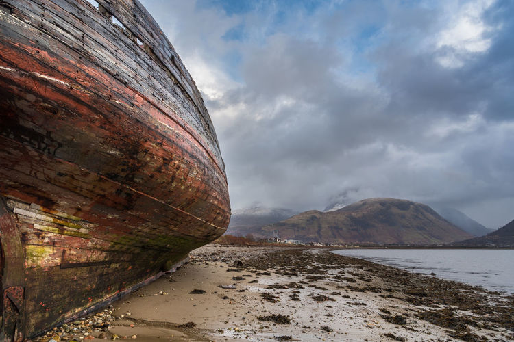 Wreck of old fishing boat and view towards Fort William, Highland and the snow capped peak of Ben Nevis from the shore of Loch Linnhe at Corpach, Scottish Highlands. **The boat was originally named MV Dayspring, and built in 1975 as a fishing boat, bringing in mackerel and herring. New owners renamed the ship the Golden Harvest. **Her final voyage took place in 2001. The boat slipped its moorings at Kinlochleven Pier after a heavy storm and has lain in the same spot since the 8th December 2011. Photographed on the 8th December 2017. Ben Nevis Corpach Scotland Wreck Abandoned Boat Cloud - Sky Day Nature No People Outdoors Shore Sky The Higlands Water
