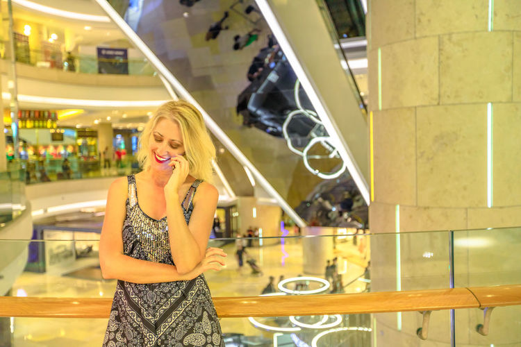 Blonde elegant woman inside Singapore most luxury glamorous shopping complex on Orchard Road, talking with mobile phone. Happy caucasian lifestyle lady shopper using a smartphone in a mall background. Singapore Singapore City Woman Tourist Tourist Attraction  Tourist Destination People Girl Females Happy Travel Hat Lifestyle Enjoy Nature Tourism Smiling Shopping Mall Shopping Mall Elegant Mobile Phone Mobile Talking Call One Person Standing Women Portrait Young Women Real People Lifestyles Indoors  Young Adult Looking At Camera Casual Clothing Leisure Activity Happiness Front View Hair Waist Up Fashion Beautiful Woman Hairstyle