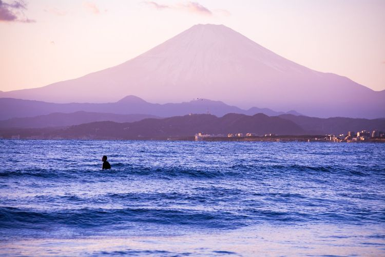 Silhouette Man Swimming In Sea Against Mt Fuji During Sunset