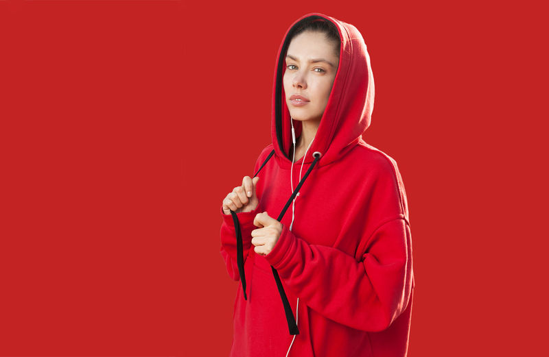 Beautiful caucasian young woman dressed in the red hoodie Girl One Person Woman Females Young Adult Sportive Sportswear Hood HOODIES Hood - Clothing Isolated Backgrounds Sport Fitness Portrait Caucasian Europe European  Copy Space Free Space Wear Clothes Style Fashion Trend Oversized Youth Culture Red Studio Shot Colored Background Holding Adult Waist Up Looking At Camera Indoors  Music Red Background Women Standing Clothing Arts Culture And Entertainment